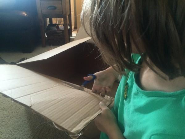 girl cutting box